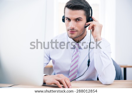 Confident male operator sitting at his workplace in office and looking at camera - stock photo