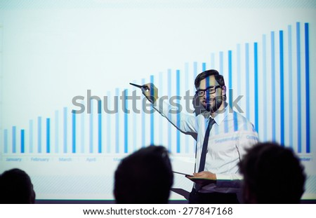 Confident male teacher presenting chart of finances to students or business people - stock photo