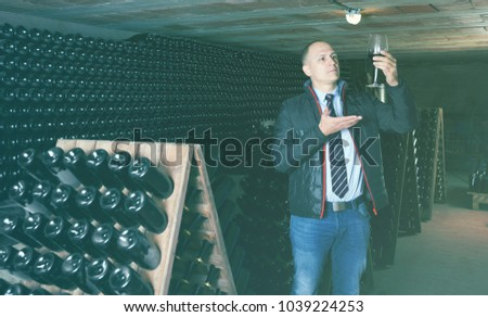 Confident male winemaker degusting red wine in wine cellar near bottles racks