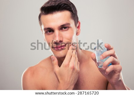 Confident man applying lotion after shave on face over gray background. Looking at camera - stock photo