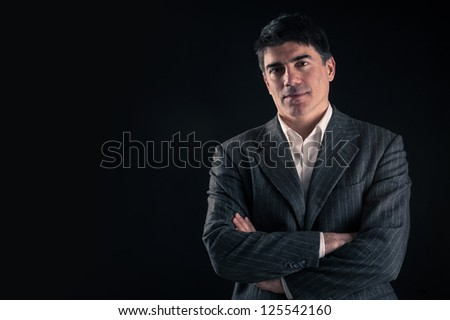Confident man close up portrait against black background with copy space. - stock photo