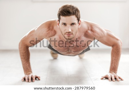 Confident man doing push-ups. Confident young muscular man doing push-ups and looking at camera - stock photo