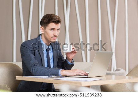 Confident Man Drinking Coffee and Working in Cafe