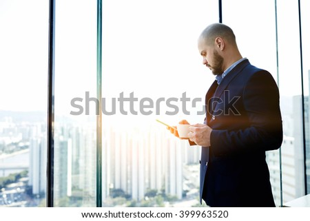 Confident man entrepreneur via mobile phone is booking on-line hotel for his future business trip abroad, while is standing with cup of coffee in hand in office interior against window with copy space - stock photo