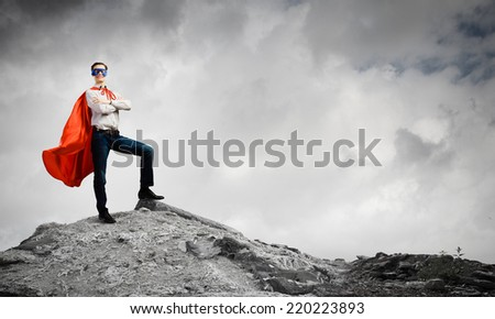 Confident man in cape and mask standing on ruins