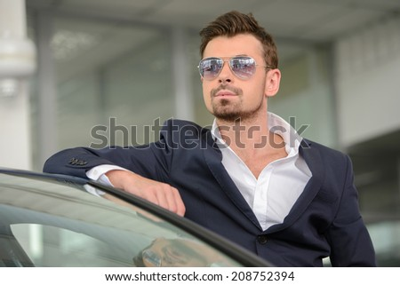 Confident man in formalwear leaning at the car and looking at camera while standing at car dealership - stock photo