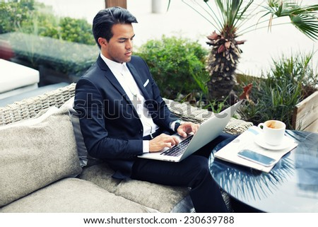 Confident man in suit typing on laptop computer keyboard, businessman seated in cafe working with computer, businesspeople using modern devises, rich businessman working with laptop computer in cafe - stock photo