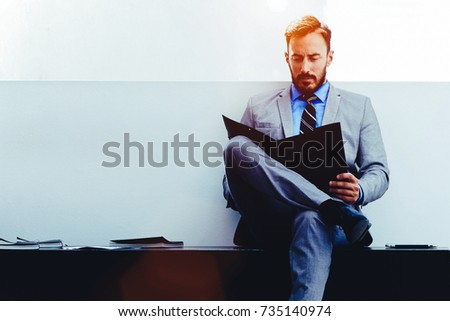 Confident man lawyer in formal wear reading paper documents while sitting in modern office space interior, young handsome male economist studying dossier files before an important meeting with partner