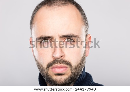 Confident man looking at camera in a grey background.