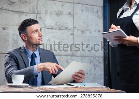 Confident man making order at restaurant - stock photo