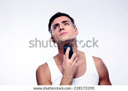 Confident man shaving with electric razor over gray background - stock photo
