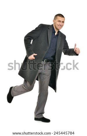 Confident man with thumb up in coat on a white background - stock photo