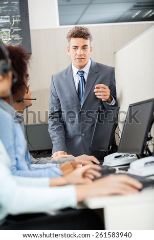 Confident manager discussing with customer service representatives in office - stock photo