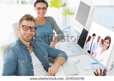 Confident manager in front of her team with folded arms against team of smiling young designers looking at camera - stock photo