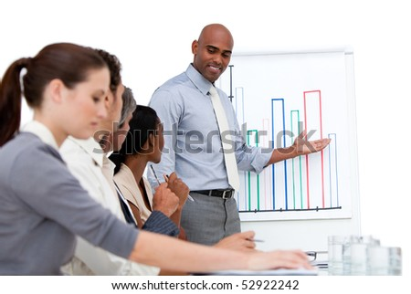 Confident manager presenting a chart explaining the results to his team in a company - stock photo