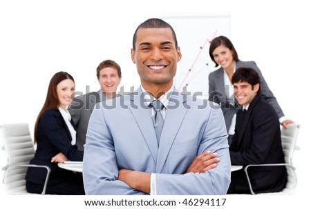 Confident manager with folded arms in front on his team in a meeting