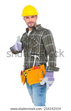 Confident manual worker gesturing thumb up on white background