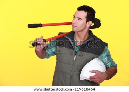 Confident manual worker holding hard hat and bolt cutter - stock photo