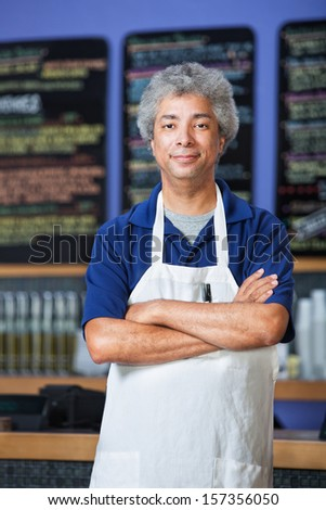 Confident mature Black cafe owner in apron  - stock photo