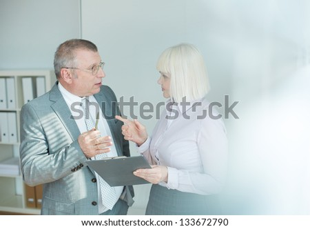Confident mature businessman and his colleague looking at one another while discussing document at meeting