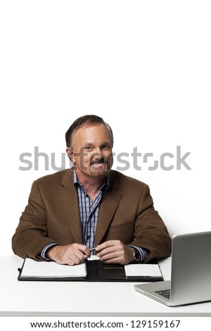 Confident mature businessman at work looking at camera