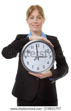 Confident mature caucasian business woman holding a large clock In her hands showing the success of good office timekeeping.