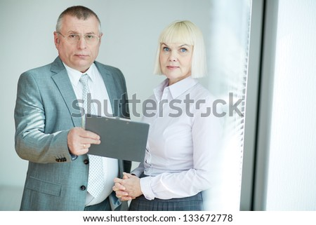 Confident mature co-workers looking at camera - stock photo