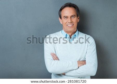 Confident mature man. Confident mature man looking at camera and smiling while keeping arms crossed and standing against grey background - stock photo