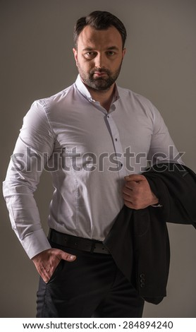 Confident mature man dressed formal looking at camera. Studio shot. - stock photo