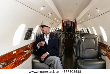 Confident mature man sitting at his seat in private airplane holding a cocktail