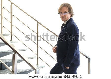 Confident mature man standing on stairs indoors