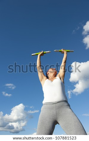 Confident mature woman exercising with weights outdoor, isolated with blue sky as background and copy space.
