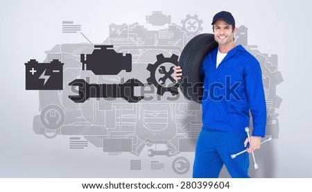 Confident mechanic carrying tire against grey vignette - stock photo