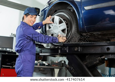 Confident Mechanic Fixing Hubcap To Car Tire - stock photo