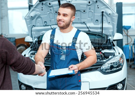 Confident mechanic. Portrait of a handsome car mechanic shaking hands with his client and holding his clipboard in the car repair station - stock photo