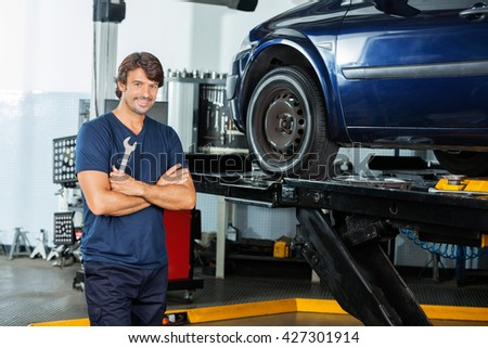 Confident Mechanic Standing Arms Crossed At Garage