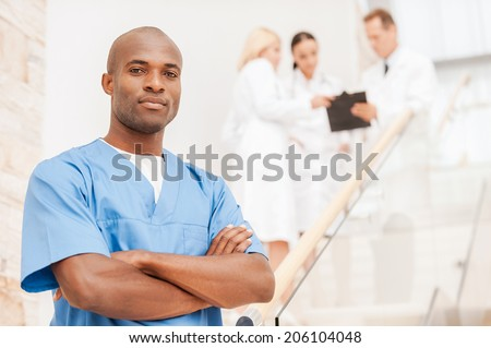 Confident medical expert. Confident African doctor in blue uniform keeping arms crossed and looking at camera while his colleagues talking in the background - stock photo