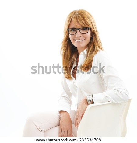 Confident middle age business woman sitting against white background.  - stock photo
