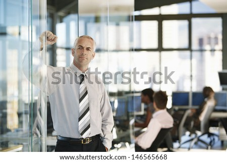 Confident middle aged businessman leaning on glass door with colleagues working in background - stock photo