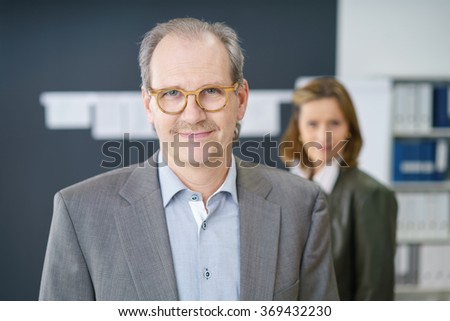 confident middle-aged businessman smiling at the camera with his female colleague in background