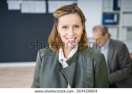 confident middle-aged businesswoman in the office with a colleague sitting in background - stock photo