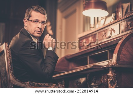 Confident middle-aged man in luxury vintage style interior  - stock photo