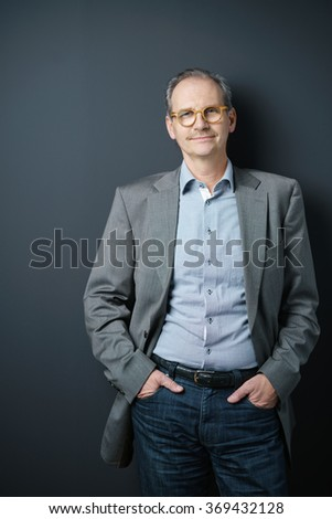 confident middle-aged man standing with hands in his pockets against grey background in studio - stock photo