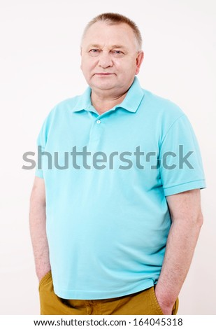 Confident middle aged man with hands in his pockets over white background - stock photo
