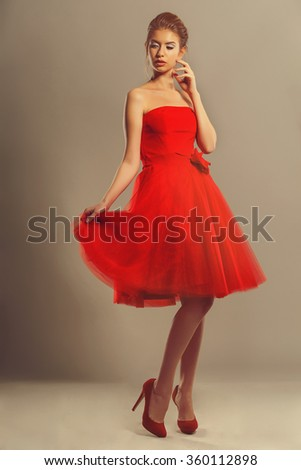 Confident model in a red flowing dress in studio