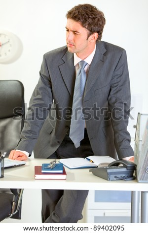 Confident modern businessman holding standing near office desk and looking in corner