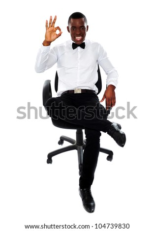 Confident modern man sitting on chair and showing okay gesture - stock photo