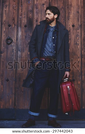 Confident modern tourist standing with vintage suitcase on wooden door background  with copy space for text message or advertising, elegant fashionable hipster man dressed in coat waiting for someone
