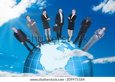Confident multiethnic business people standing on globe against blue sky.  - stock photo