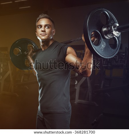 Confident muscular man training squats with barbells over head. Closeup portrait of professional bodybuilder workout with barbell at gym.  - stock photo